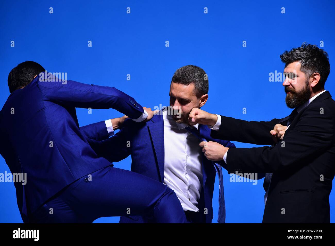 Rivalry and business confrontation concept. Coworkers decide upon best working position. Businessmen with strict faces in formal wear on blue background. Company leaders fight for business leadership Stock Photo