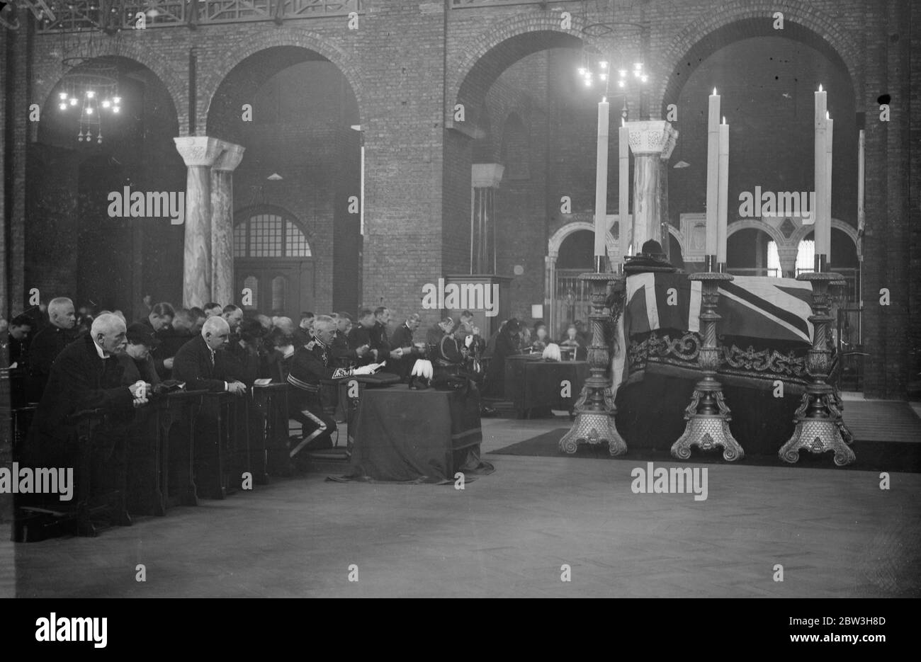 Police kneel in prayer at Westminster Cathedral . The annual armistice church parade of London ' s Roman Catholic police took place at Westminster Cathedral . As Lord Trenchard retired yesterday and Sir Philip Game , who succeeds him is unable to take over command of the present on account of an accident , Sir Hugh Turnball , the City Police Commissioner , took the salute . Photo shows , policement kneeling in prayer at the service . 12 November 1935 Stock Photo