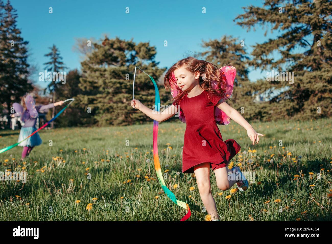 Happy children girls playing with ribbons in park. Cute adorable kids running on meadow playing together. Outdoor summer backyard activity for kids. H Stock Photo