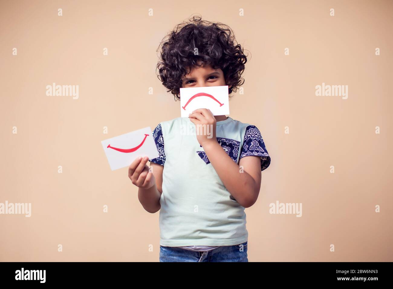 A portrait of kid boy holding cards with positive and negative symbol. Children and emotions concept Stock Photo
