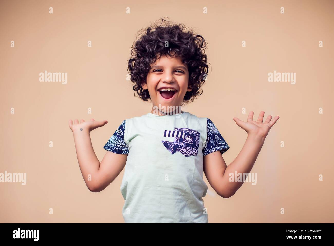 A portrait of surprised kid boy with curly hair. Children and emotions concept Stock Photo