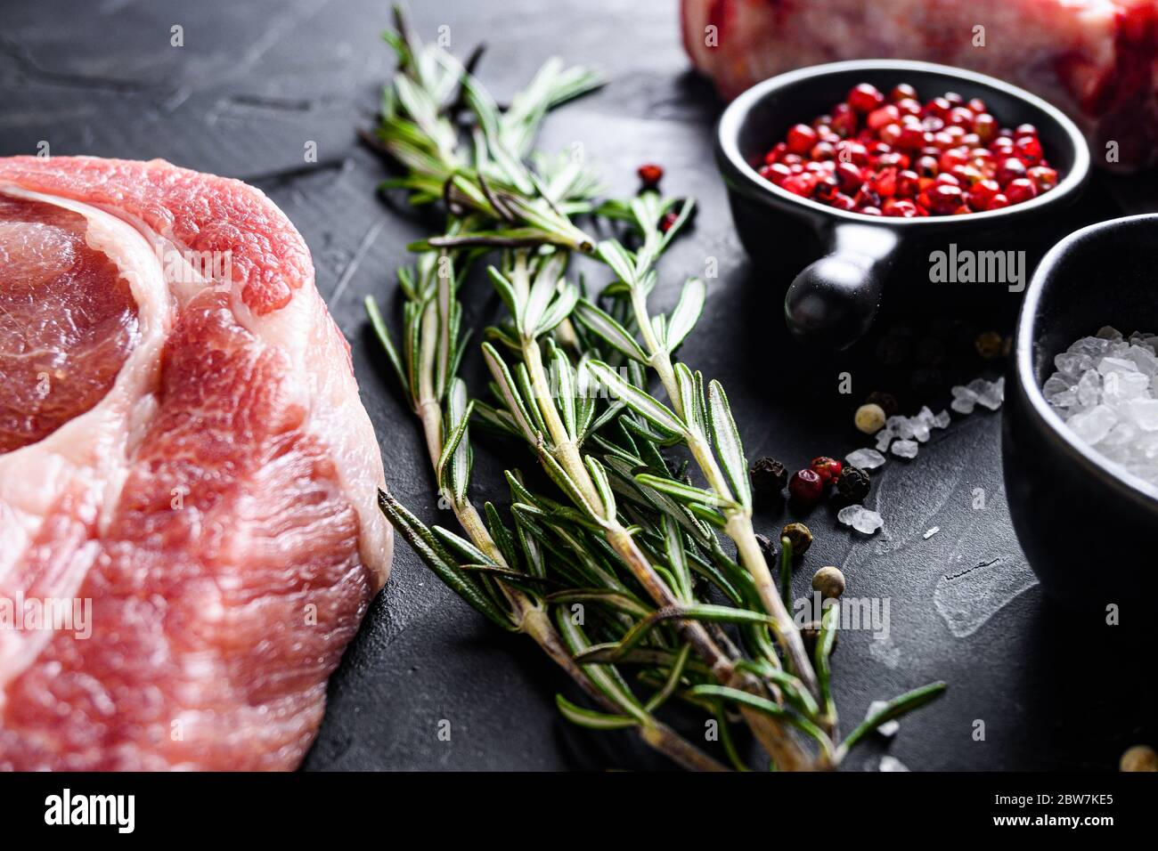 Rosemary herbs close up on black stone table with spices and raw meat near side view selective focus. Stock Photo