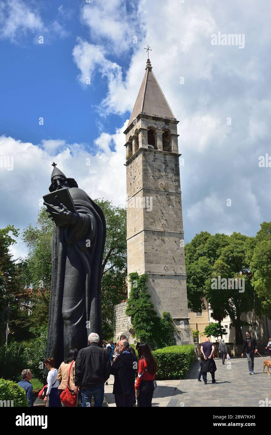 SPLIT, CROATIA - APRIL 29, 2019: Monumental bronze statue of Bishop Gregory of Nin created in 1929 by Ivan Mestrovic and The bell tower and the Chapel Stock Photo
