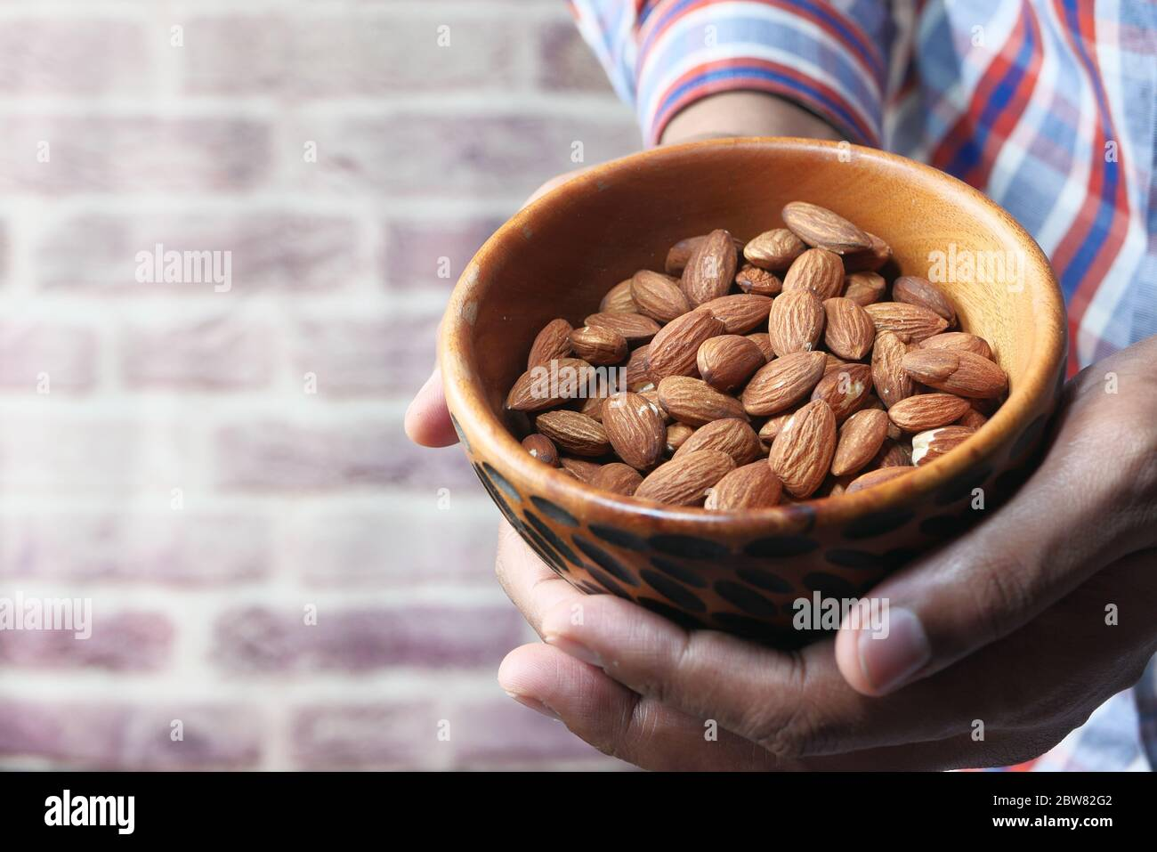 Close up of man hand holding a bowl of almond with copy space  Stock Photo