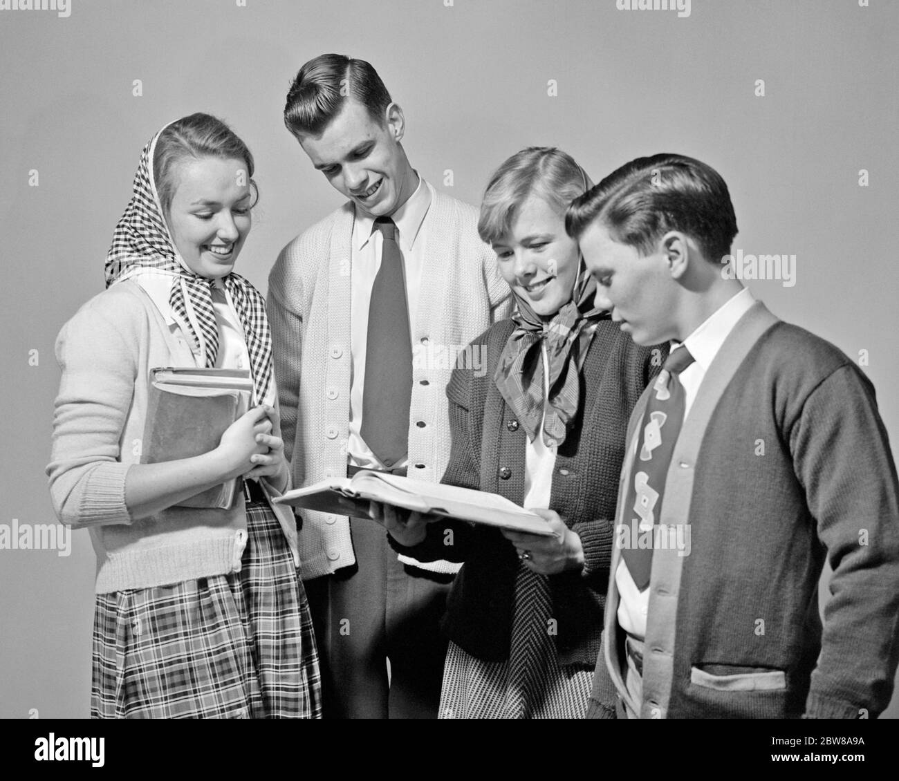 1950s 4 Senior High School Boys And Girls Looking At New Text Book Wearing Sweaters Boys Have Neckties Girls Head Scarves S4967 Lan001 Hars Old Fashion Juvenile Style Communication Friend Information