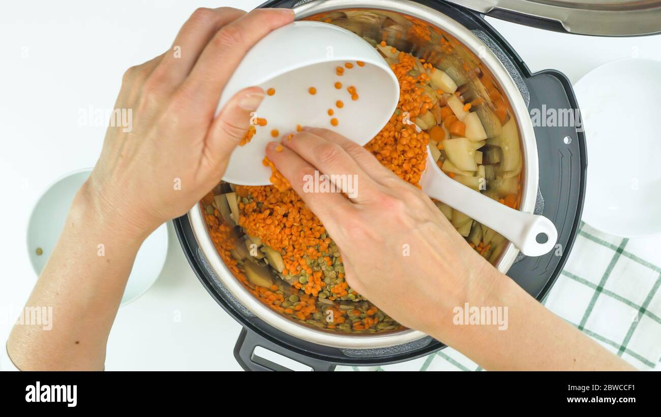 Red lentils, green lentils, and some ingredients close up in a pot. Multi cooker lentil soup rscipe Stock Photo