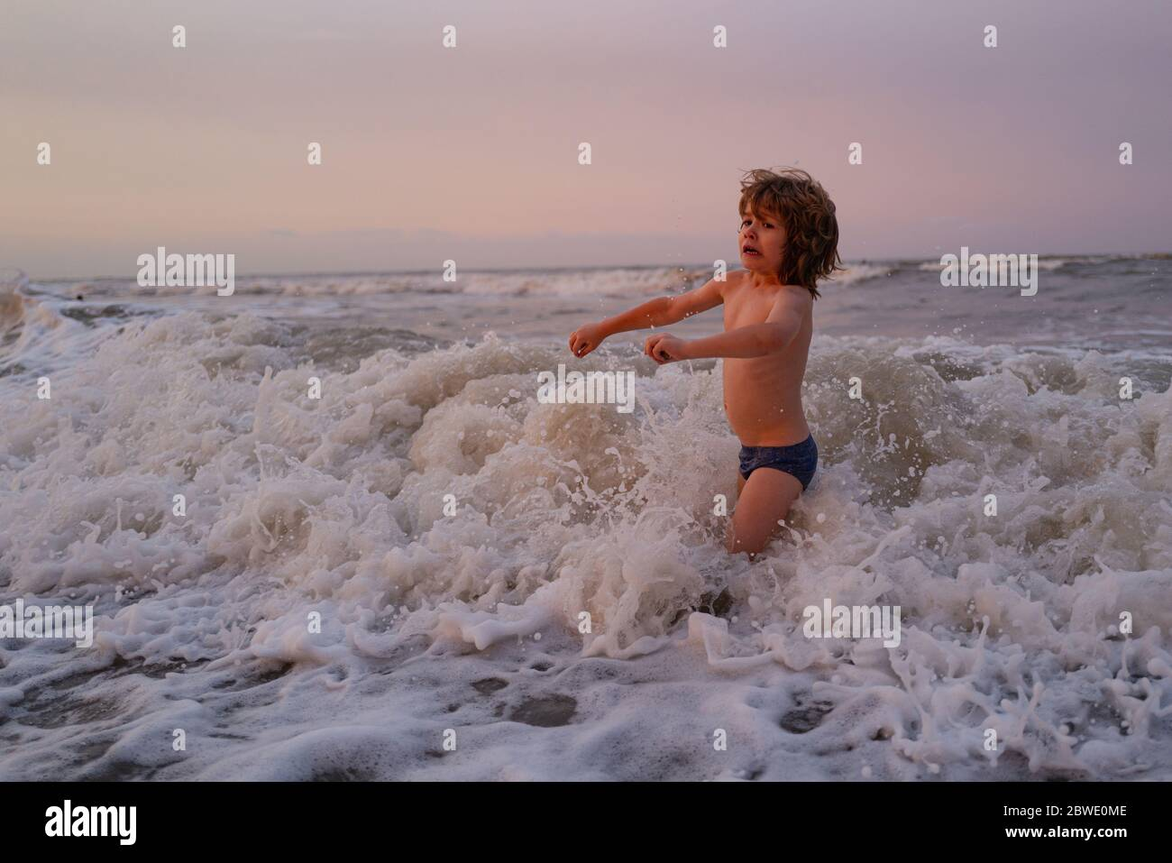 Kids jumping near the waves. Happy kids have fun in sea on beach. Travel lifestyle, swimming activities in family summer camp. Stock Photo