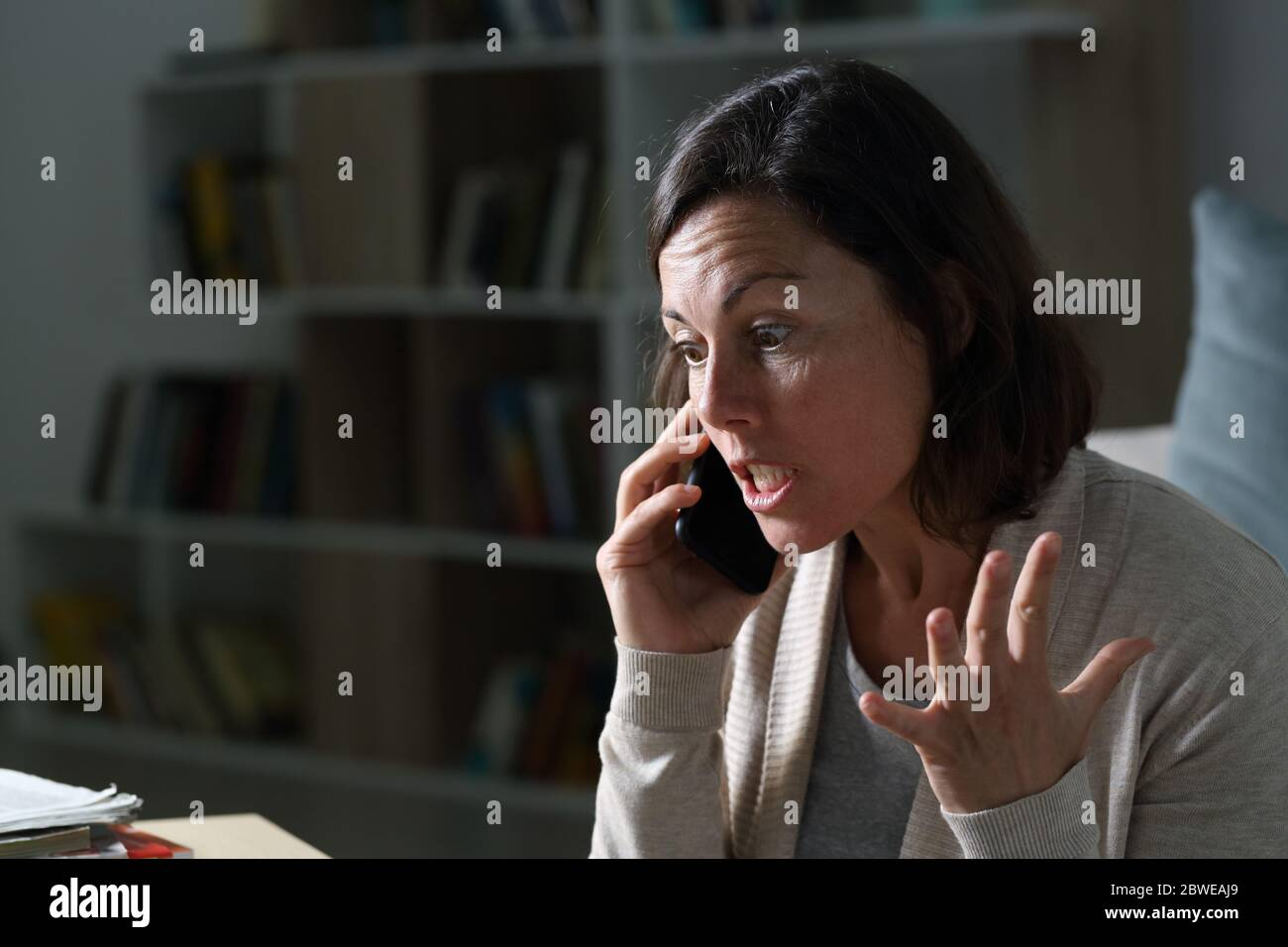 Angry middle age woman calling on smart phone sitting in the livingroom at night at home Stock Photo
