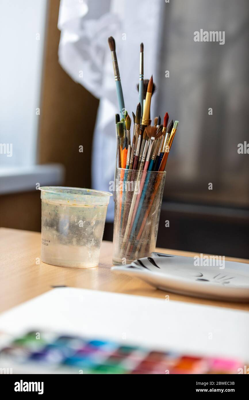 Art brushes for painting in a glass cup on the desktop. Stock Photo