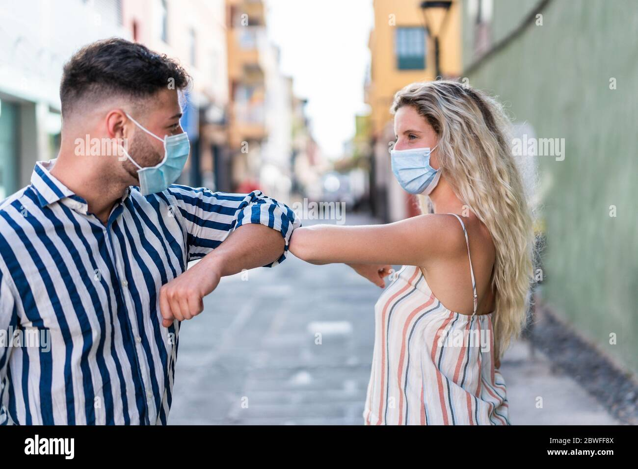 Young people bump their elbows instead of greeting with a hug - Avoid the spread of coronavirus concept - Focus on elbows Stock Photo