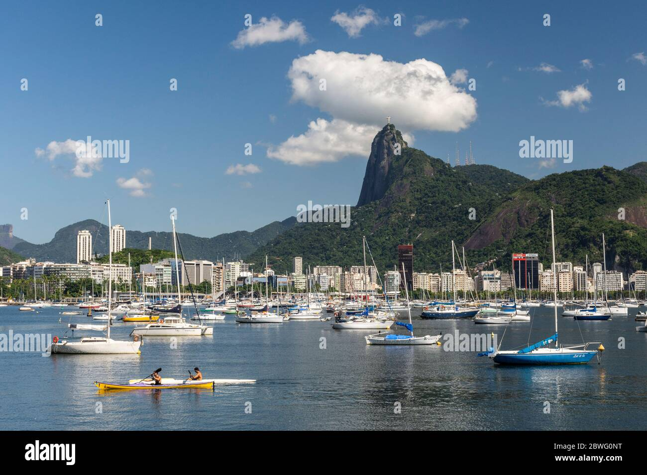 Beautiful view to man kayaking, docked sail boats and Corcovado Mountain with Christ the Redeemer Statue, Rio de Janeiro, Brazil Stock Photo