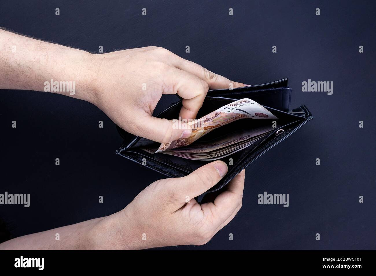 A man is holding an open wallet with money in his hands. Hands take out bills from his wallet. The concept of rejection of paper money, inflation, fin Stock Photo