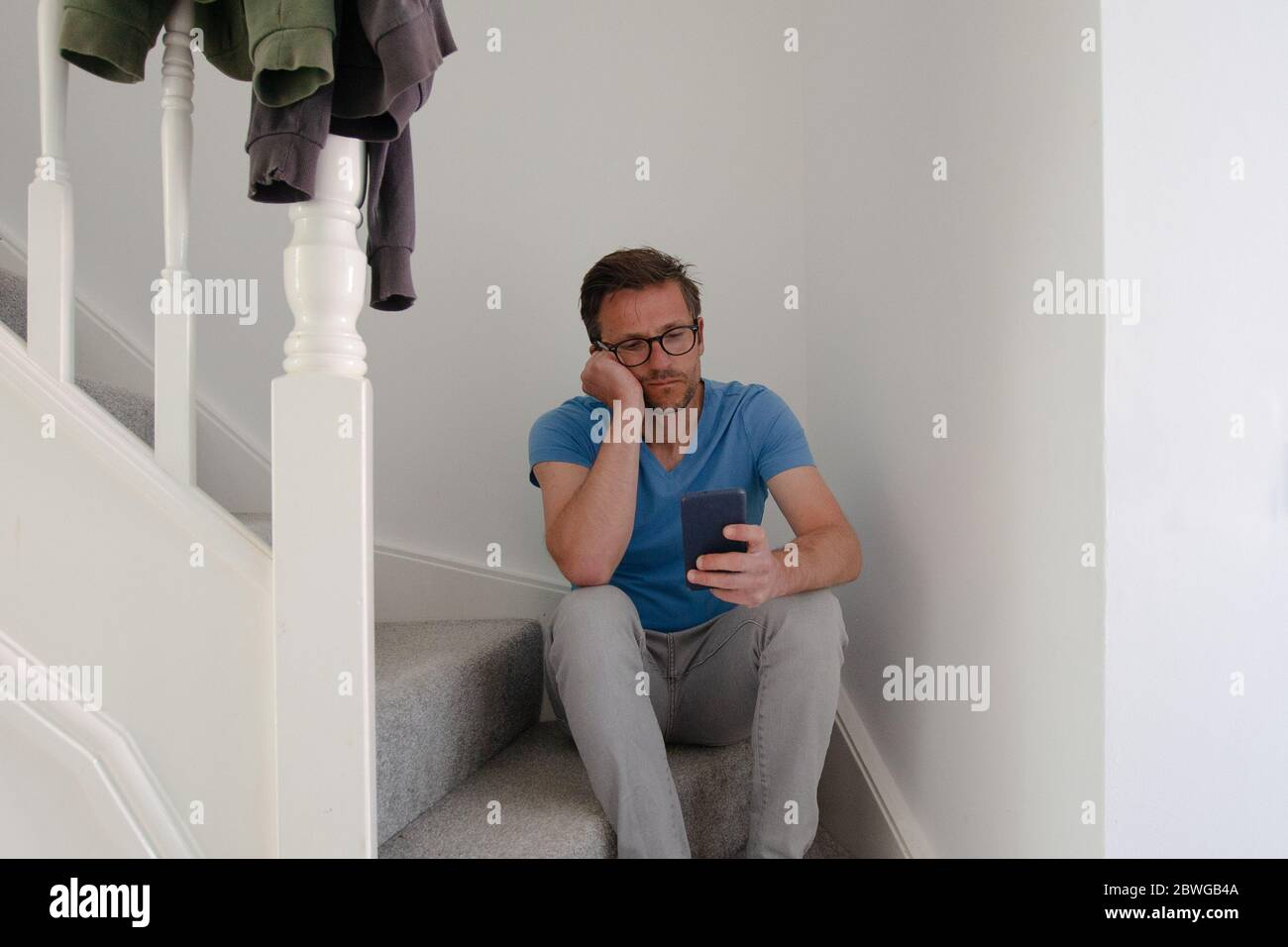 Man struggling with depression sitting on stairs Stock Photo