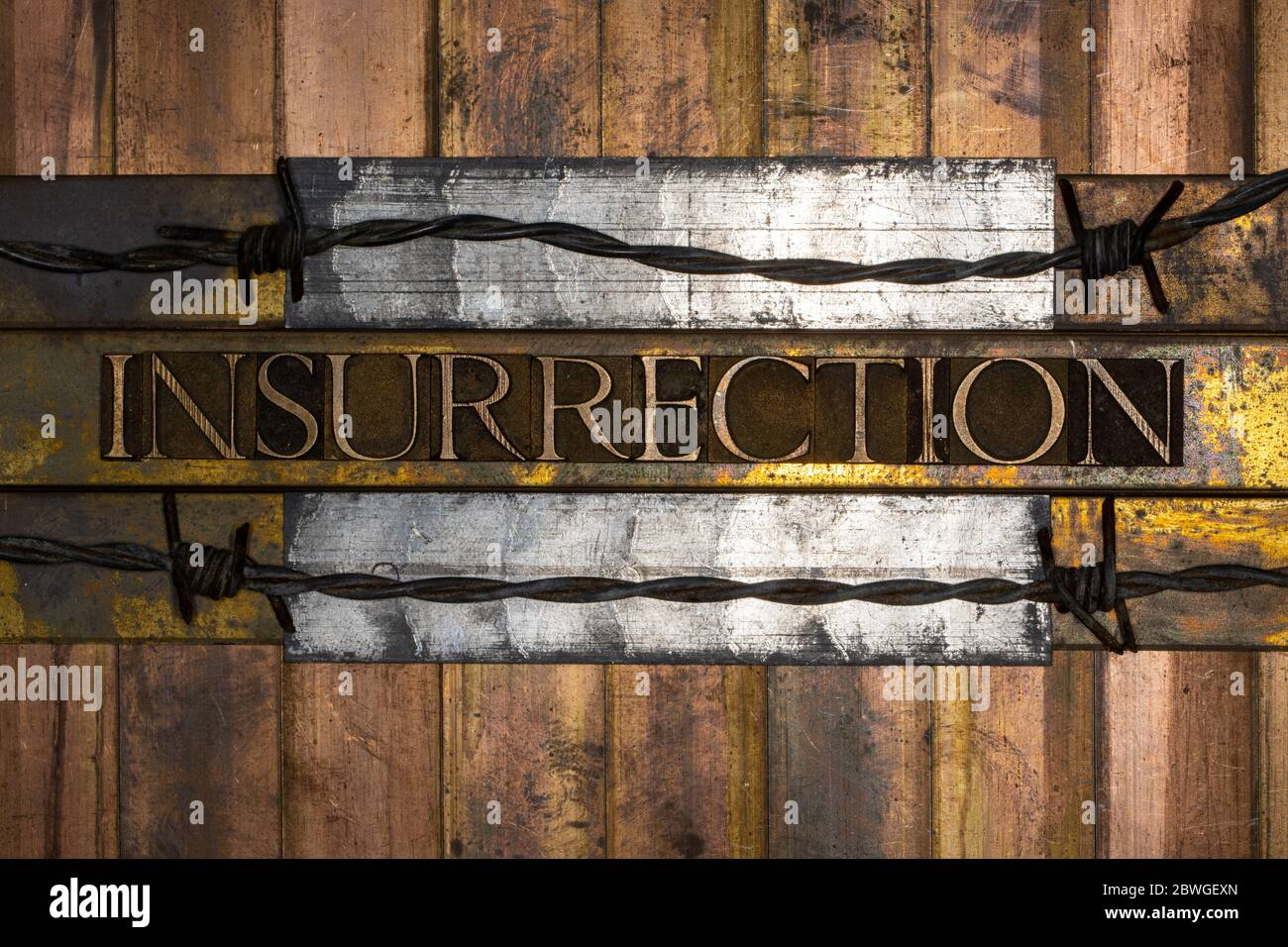 Photo of real authentic typeset letters forming Insurrection text with barbed wire on vintage textured silver grunge copper and gold background Stock Photo
