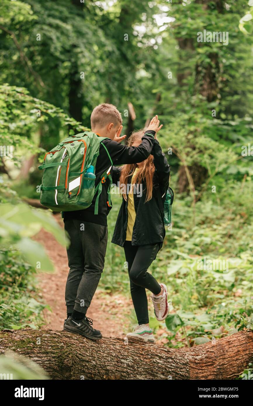 Happy boy and girl go hiking with backpacks on forest road bright sunny day. Happy children having fun together, spending great time in nature. Stock Photo