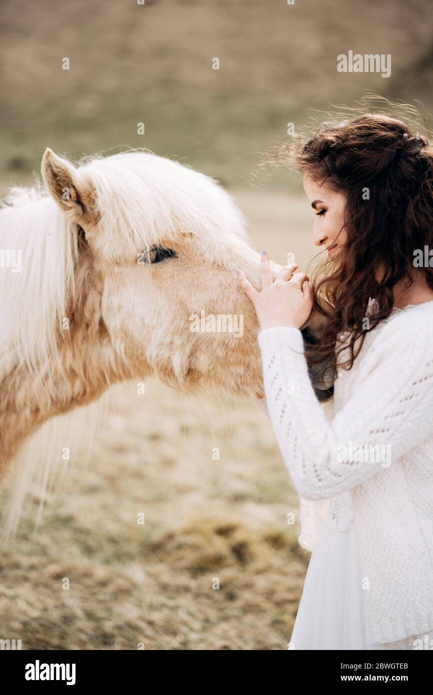 The Bride In A White Wedding Dress Strokes A White Horse In The Face Destination Iceland Wedding Photo Session With Icelandic Horses Stock Photo Alamy