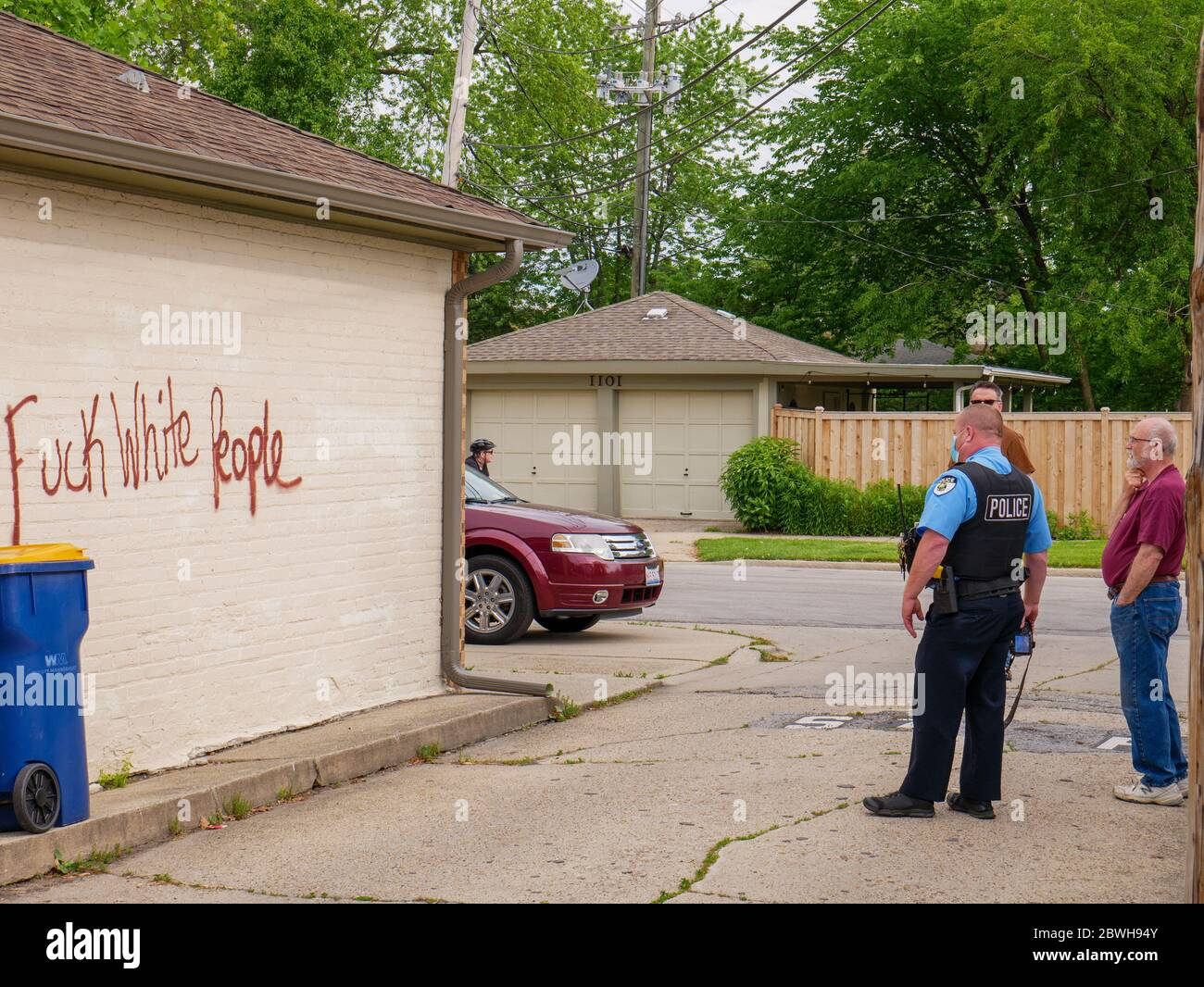 Oak Park, Illinois. 1st June 2020. An Oak Park Police evidence technician investigates racist graffiti that appeared overnight on some garages on the north side of this Chicago suburb. Evidently, the purpetrators knew who lived on each tagged property as both anti-white and anti-black graffiti was used on selected properties and varied with the race of the homeowners. Stock Photo