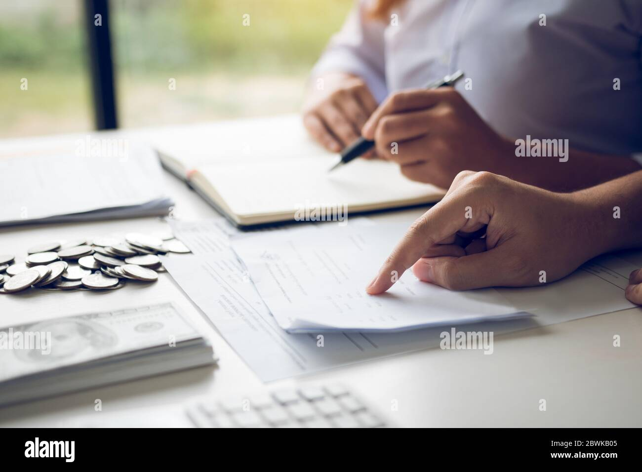Two asian couples and men and women are together analyzing expenses or finances in deposit accounts and daily income sources with an savings economica Stock Photo