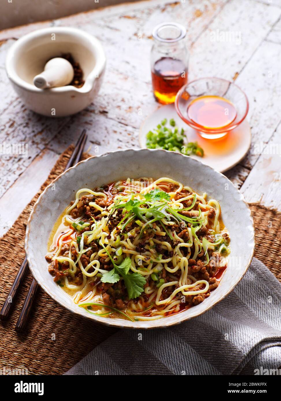Traditional Sichuan (Szechuan) Chinese Dan Dan Noodles with Minced Pork on traditional backdrop Stock Photo