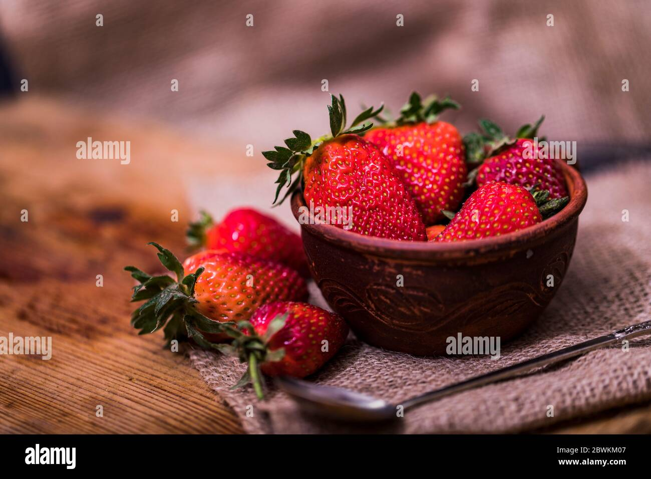 Fresh strawberries in a bowl on wooden table with low key scene. Stock Photo