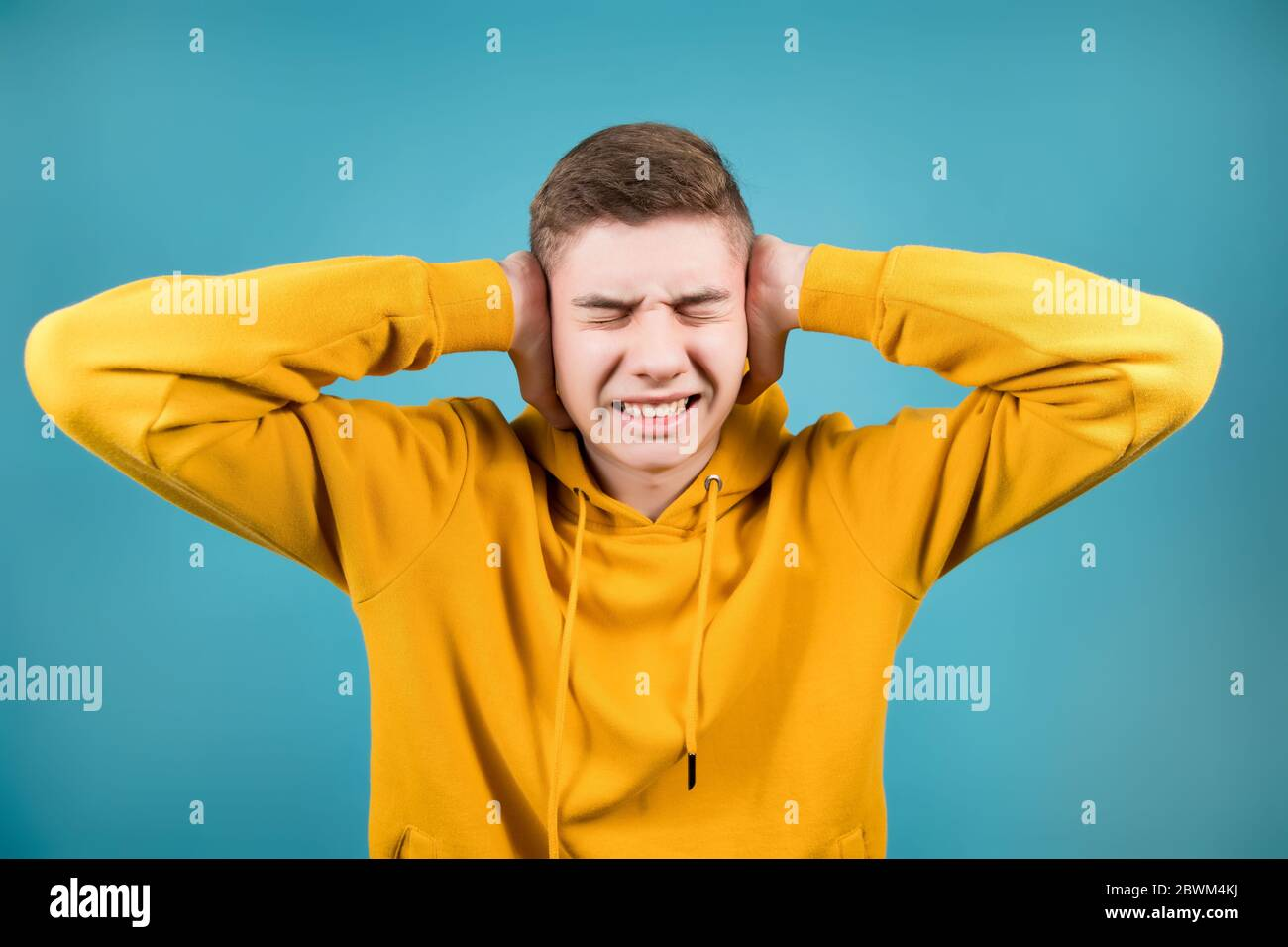 young guy in a yellow sweatshirt pinches his head and ears with his hands, squinting his eyes Stock Photo