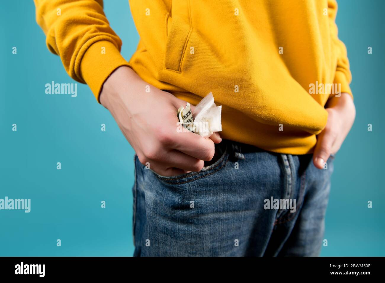 young guy takes out or puts crumpled dollars and a drug bag in his jeans pocket. Close up, no face Stock Photo