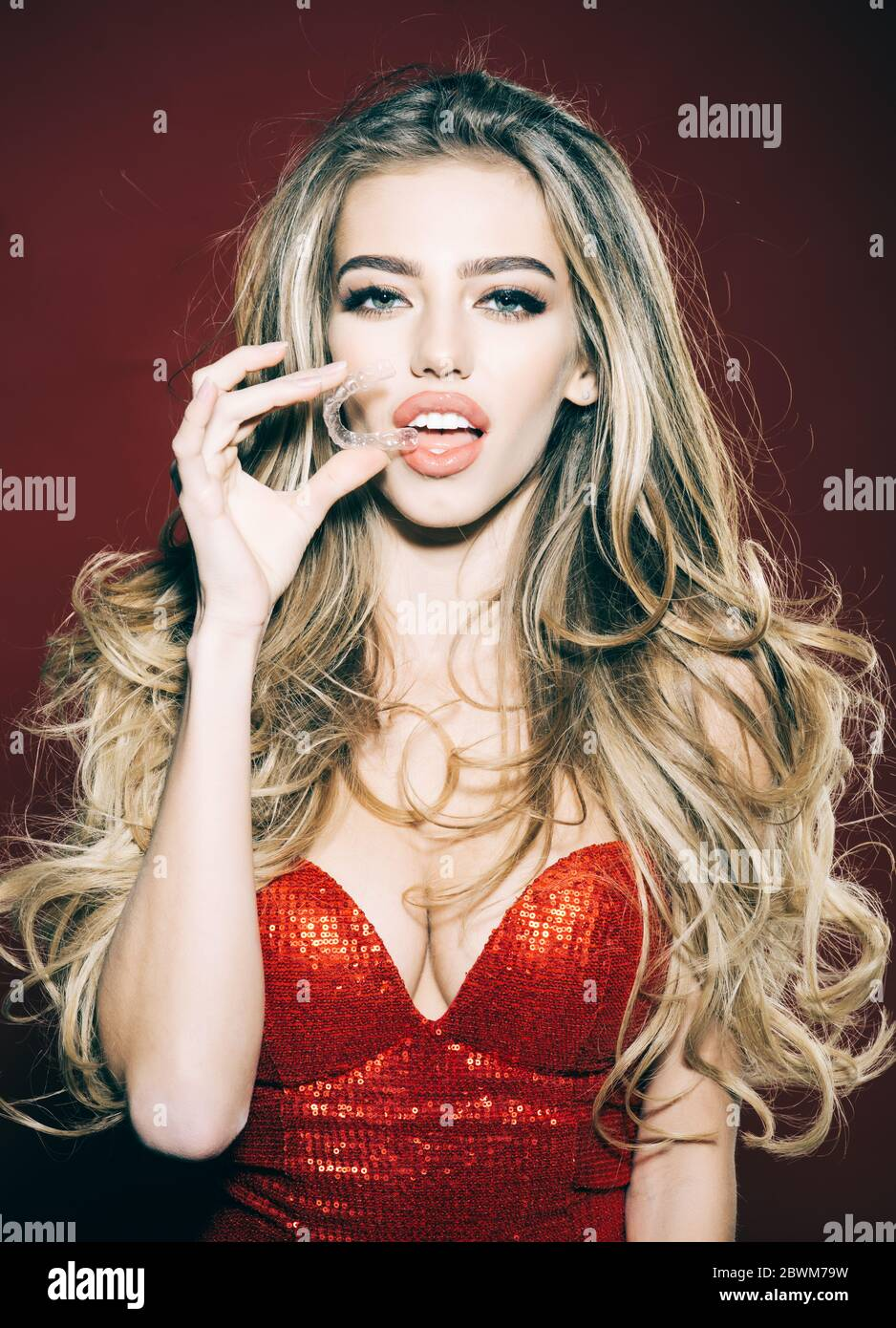 Gorgeous Woman putting transparent retainer in teeth. Plastic transparent retainer. Stomatology. Orthodontic devices. Girl in red dress holds mobile o Stock Photo