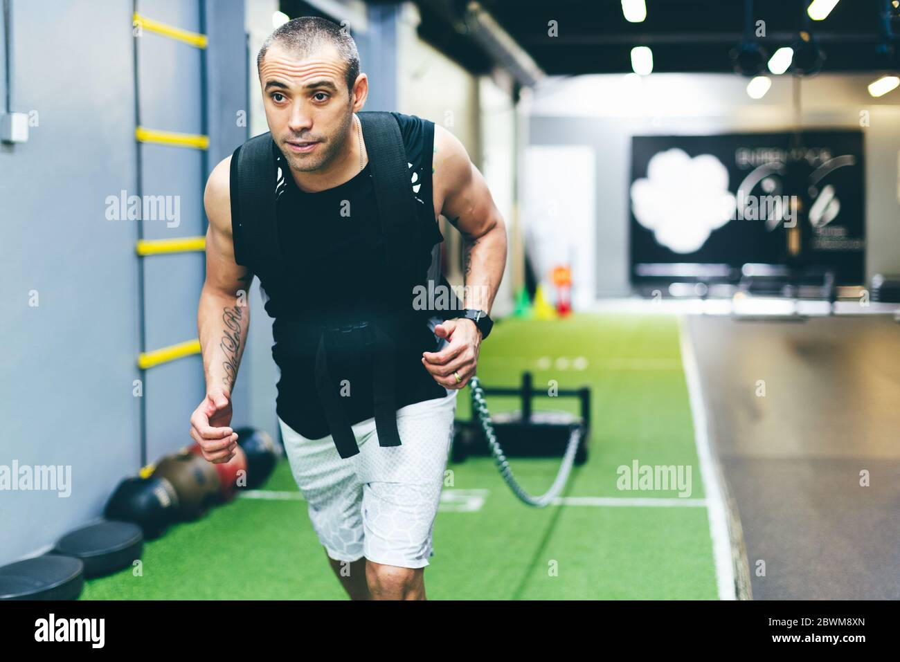 Latin boy doing physical exercise in gym dragging a sled with weight. Training concept Stock Photo