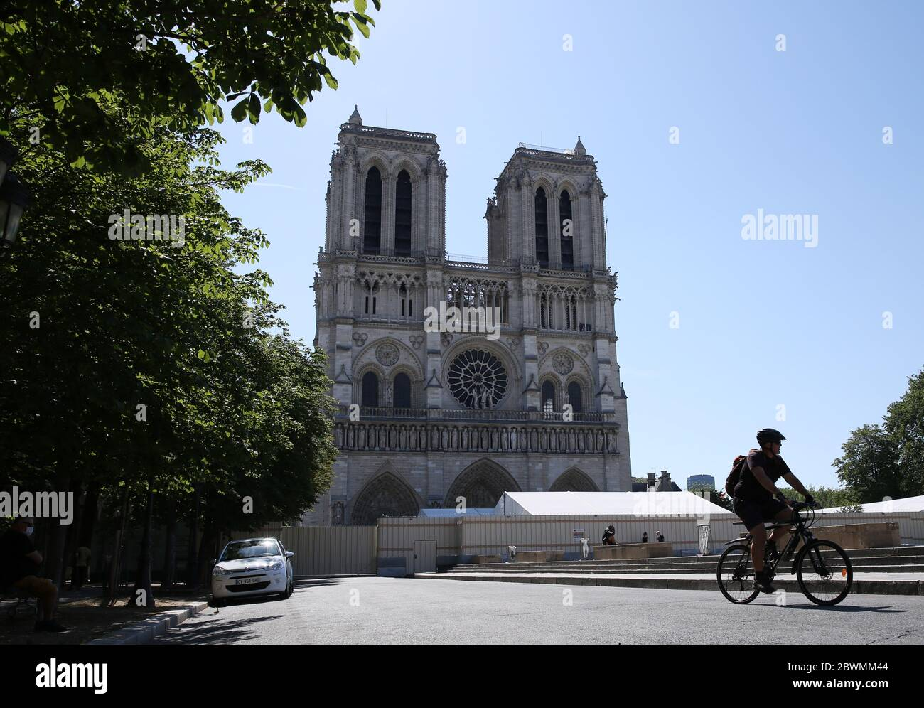 Paris, June 2. 15th Apr, 2019. A man rides a bike in front of the Notre-Dame Cathedral in Paris, France, June 2, 2020. The Parvis Notre-Dame was reopened to the public from May 31 after more than one year's close because of the huge fire on April 15, 2019. Credit: Gao Jing/Xinhua/Alamy Live News Stock Photo