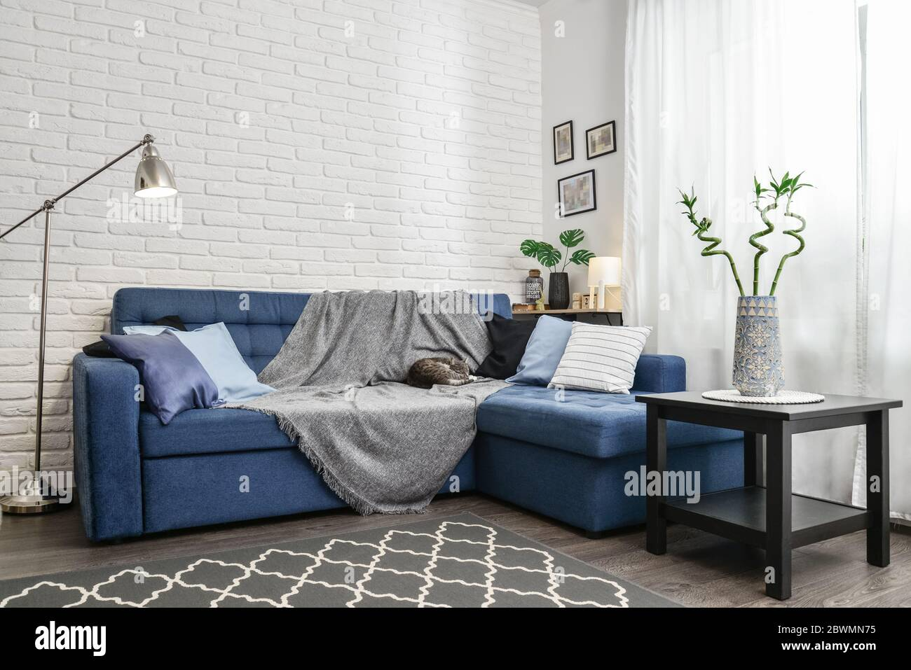 Bright Living Room In Scandinavian Style With Blue Couch Decorative Pillows White Brick Wall And White Curtains Design Interior Concept Stock Photo Alamy