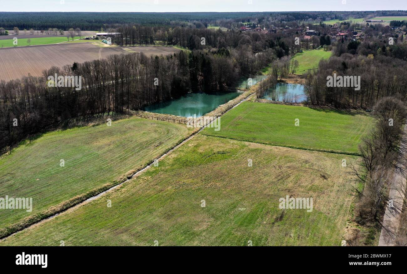 Aerial view of an agricultural meadow with two rectangular fish ponds and dark trees Stock Photo