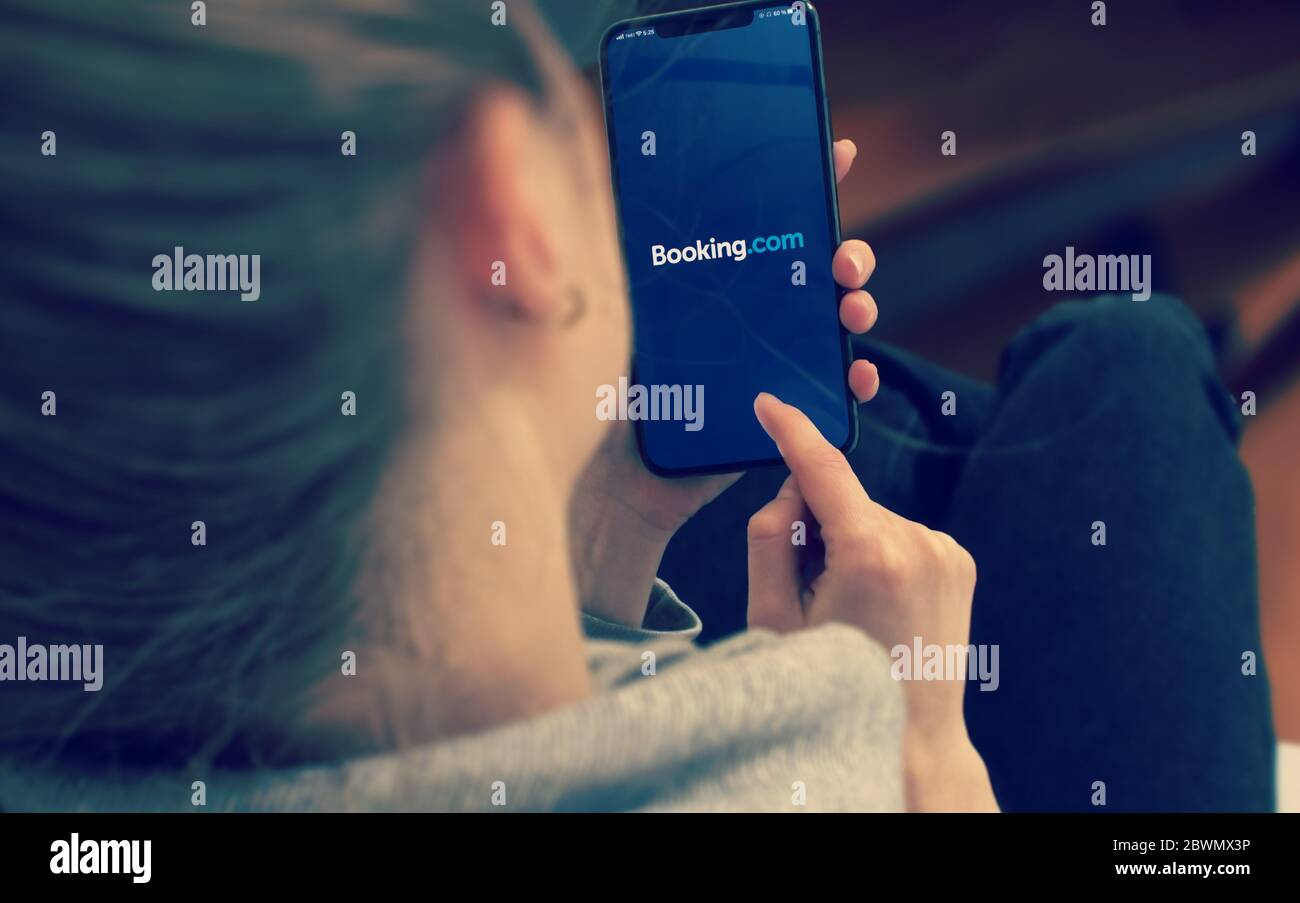 KYIV, UKRAINE-JANUARY, 2020: Booking on Mobile Phone Screen. Young Girl Pointing or Texting Smart Phone During a Pandemic Self-Isolation and Coronavirus Prevention. Stock Photo