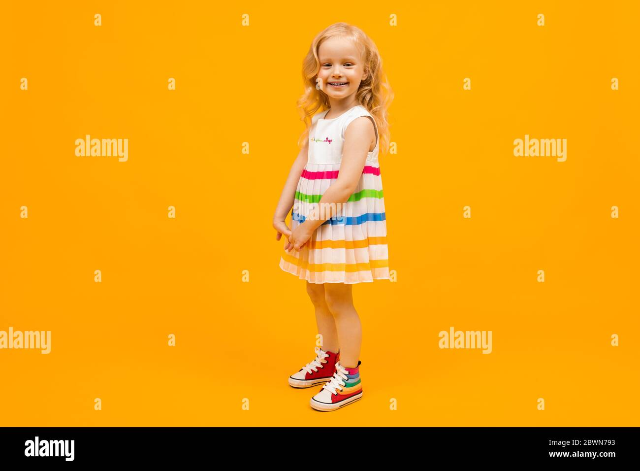 blond girl in a bright striped summer dress in full growth on an orange background Stock Photo