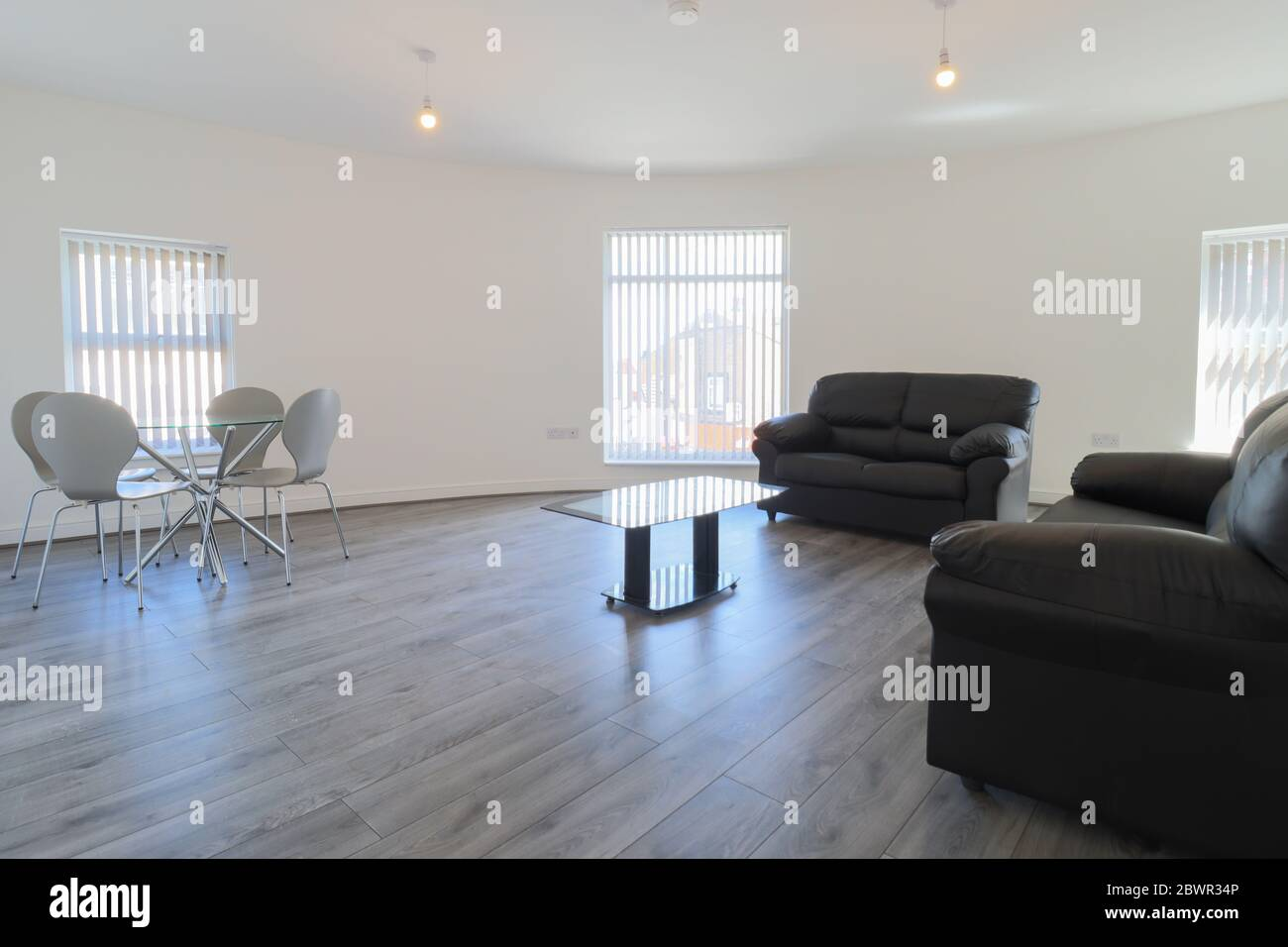 A Modern British Living Room With Two Black Leather Sofas And A Dining Table On A Grey Wooden Floor With White Walls And Modern Blinds Up At The Windo Stock Photo