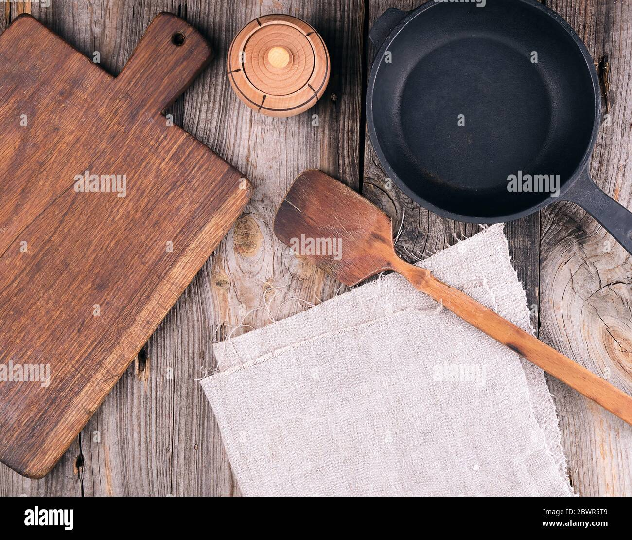 Empty Black Round Cast Iron Pan With Handle Wooden Cutting Board And Knife On A Gray Table Top View Stock Photo Alamy