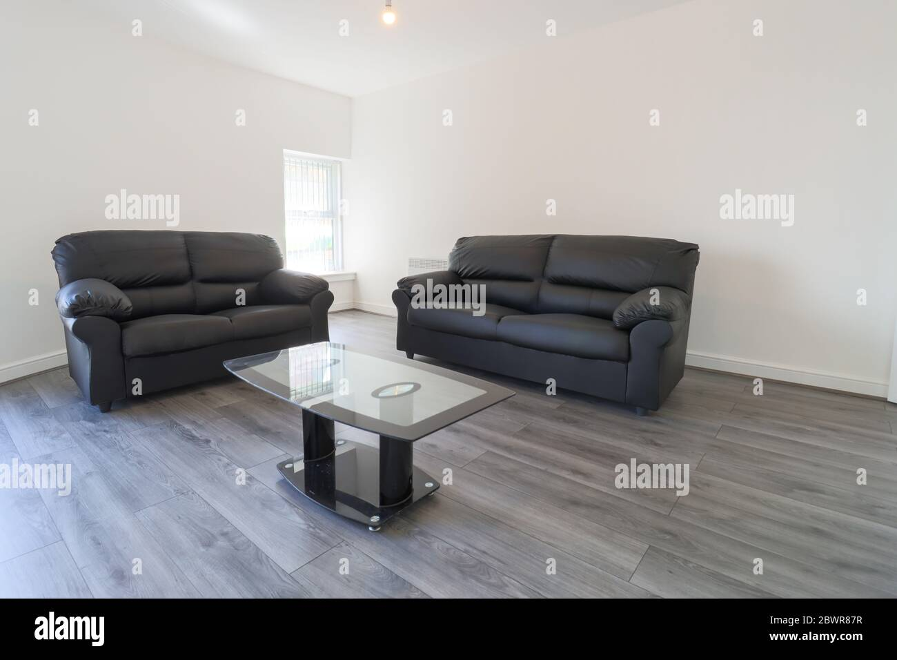 Picture of: A Modern British Living Room With Two Black Leather Sofas On A Grey Wooden Floor With White Walls And Modern Blinds Up At The Window Stock Photo Alamy