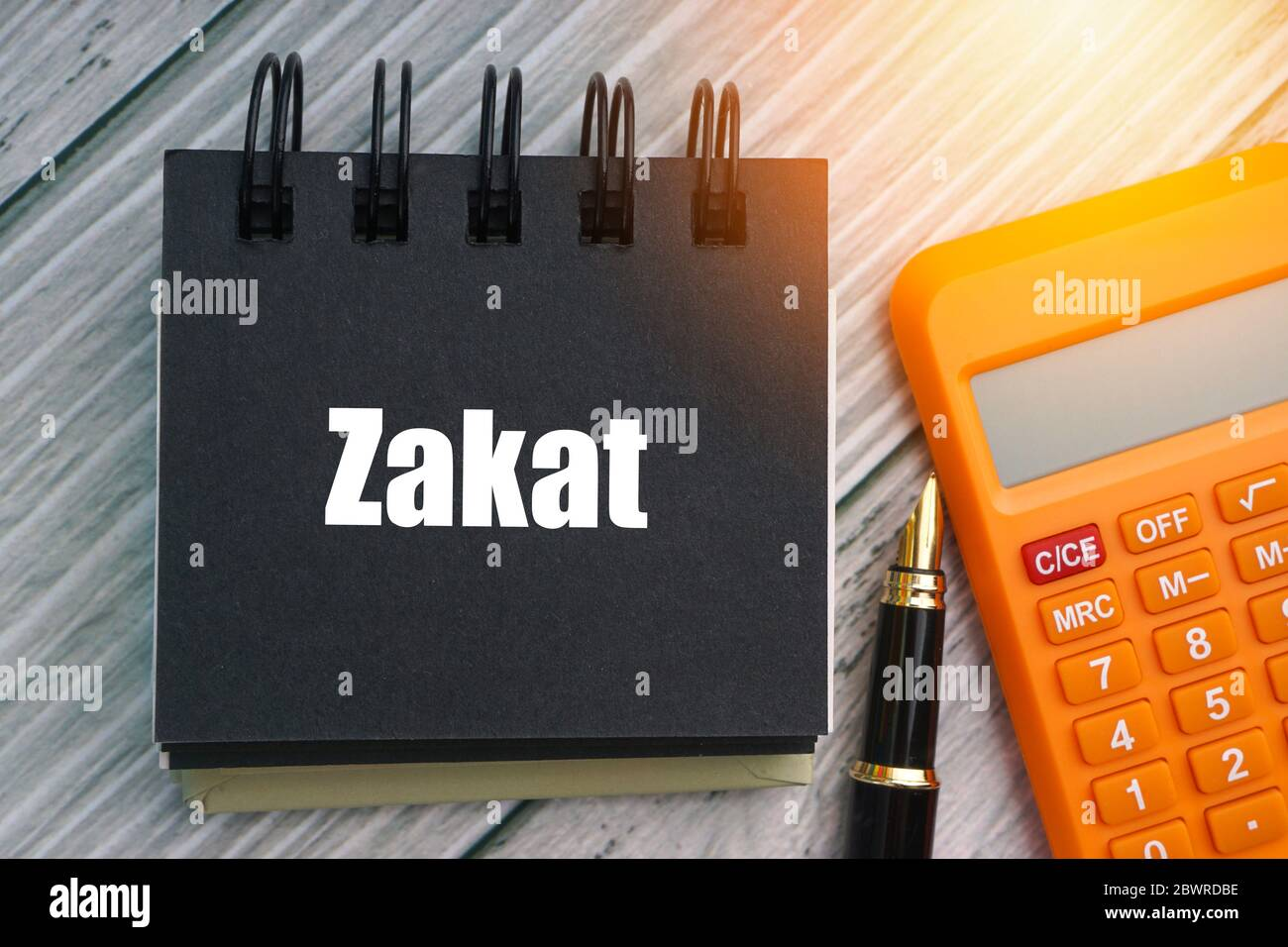 zakat or islamic tax text with fountain pen calculator and notepad on wooden background zakat is a form of alms giving treated in islam as a religi stock photo alamy alamy