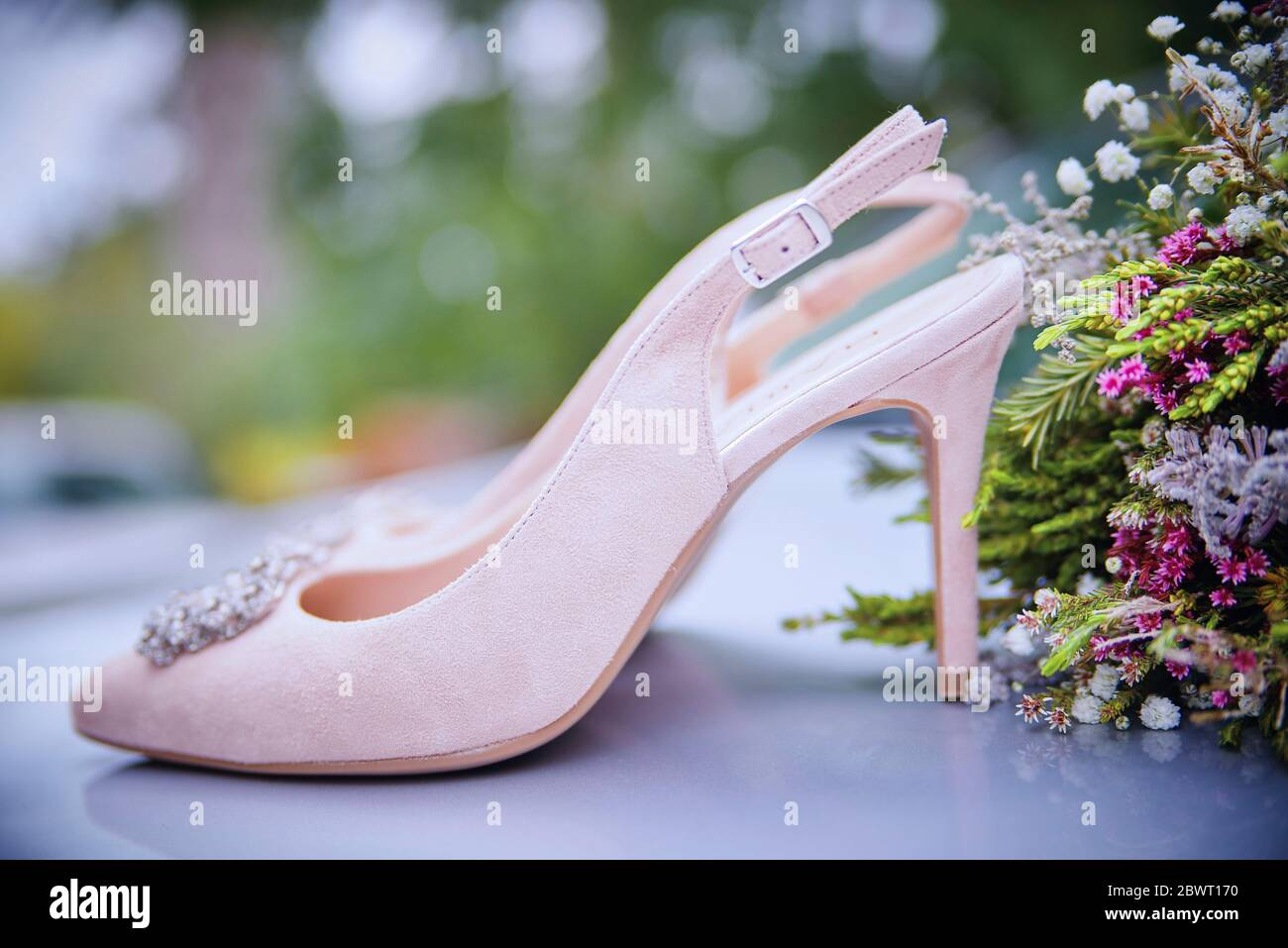 Detail of wedding shoes next to bouquet