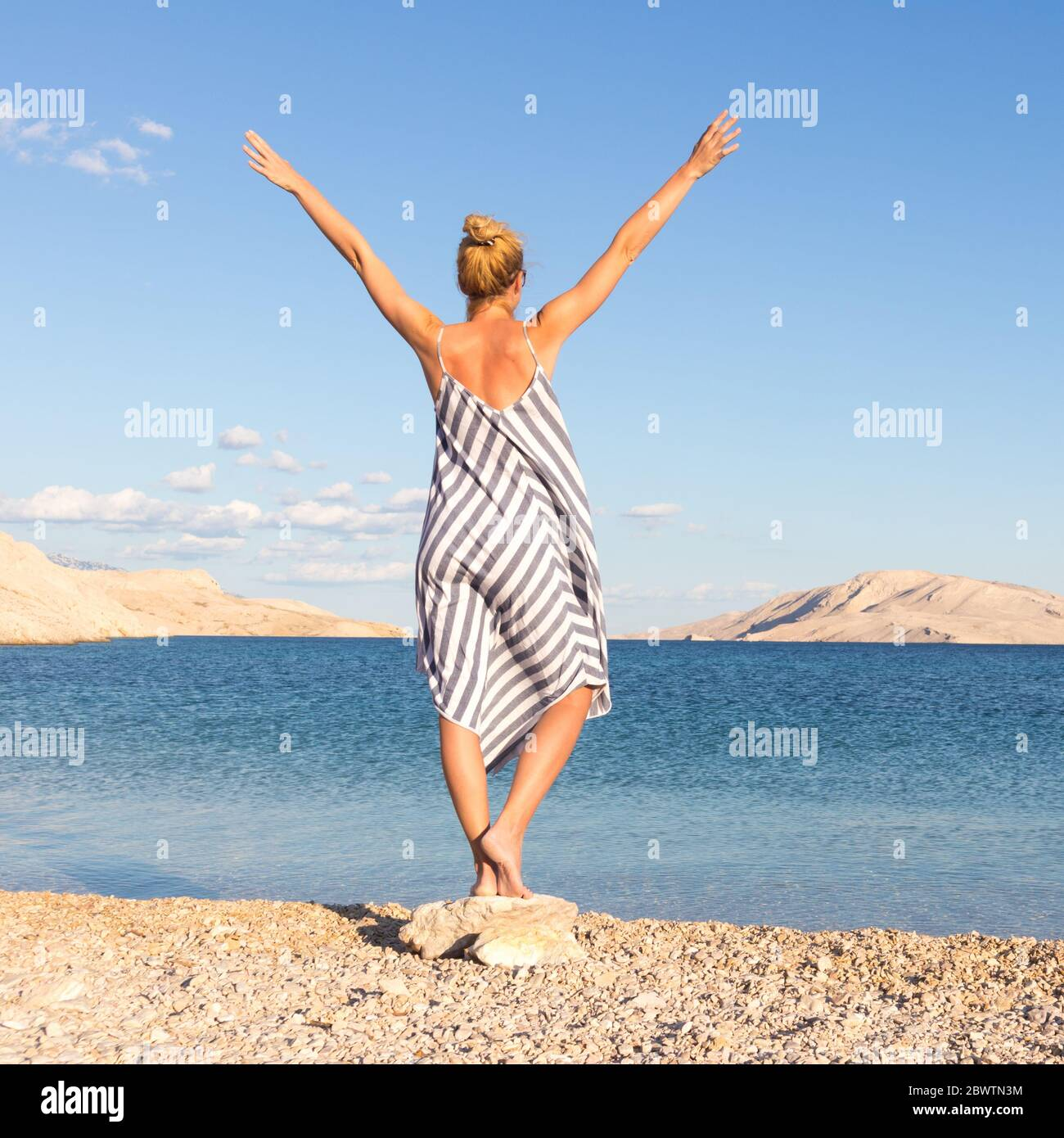 Happy carefree woman rising arms, wearing beautiful striped summer dress enjoying late afternoon on white pabbled beach on Pag island, Croatia Stock Photo