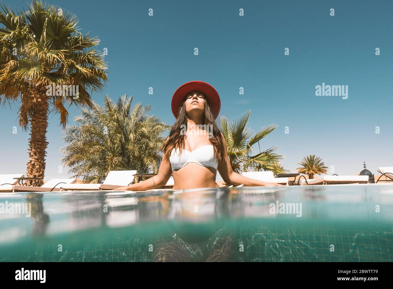 Portrait of young woman relaxing in swimming pool, Morocco Stock Photo