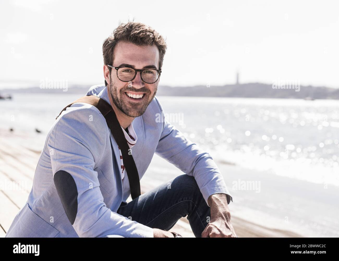 Portrait of happy young man sitting on the waterfront Stock Photo