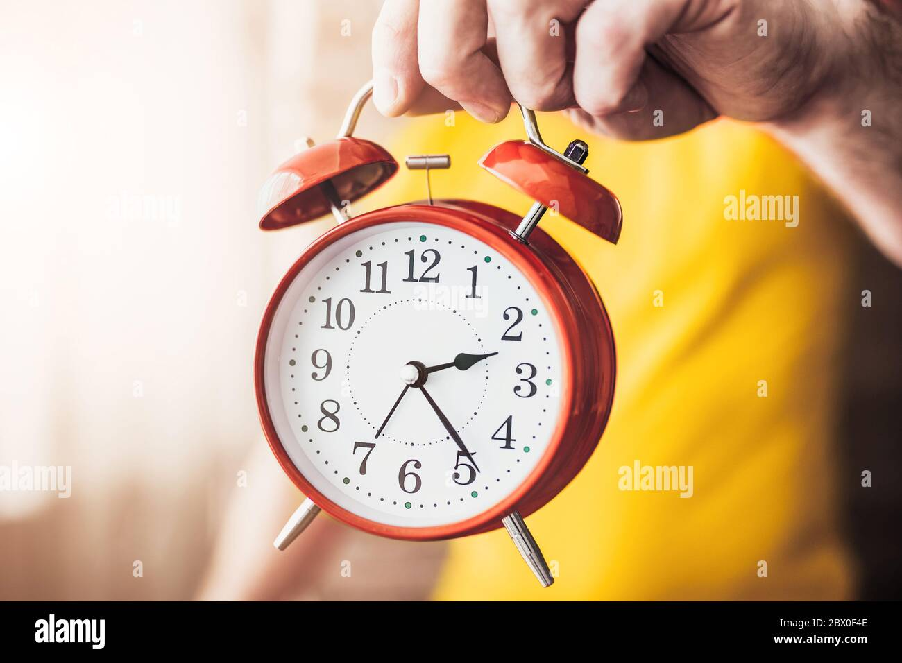 Cause time, rest time - A man keeps an alarm clock and shows time - concept - do not waste time in vain Stock Photo