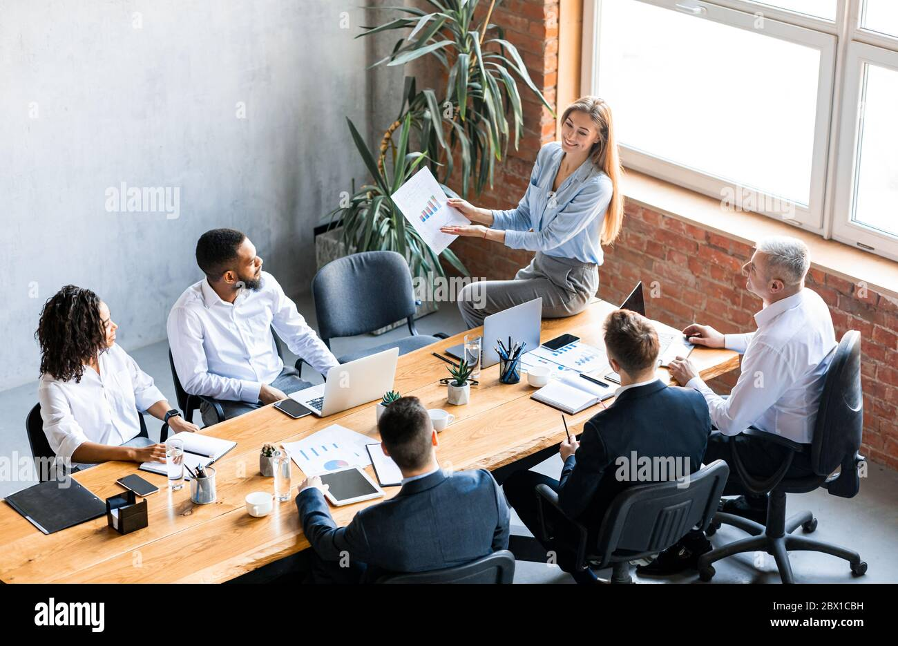 Businesswoman Showing Charts To Colleagues Analyzing Business Effectiveness In Office Stock Photo