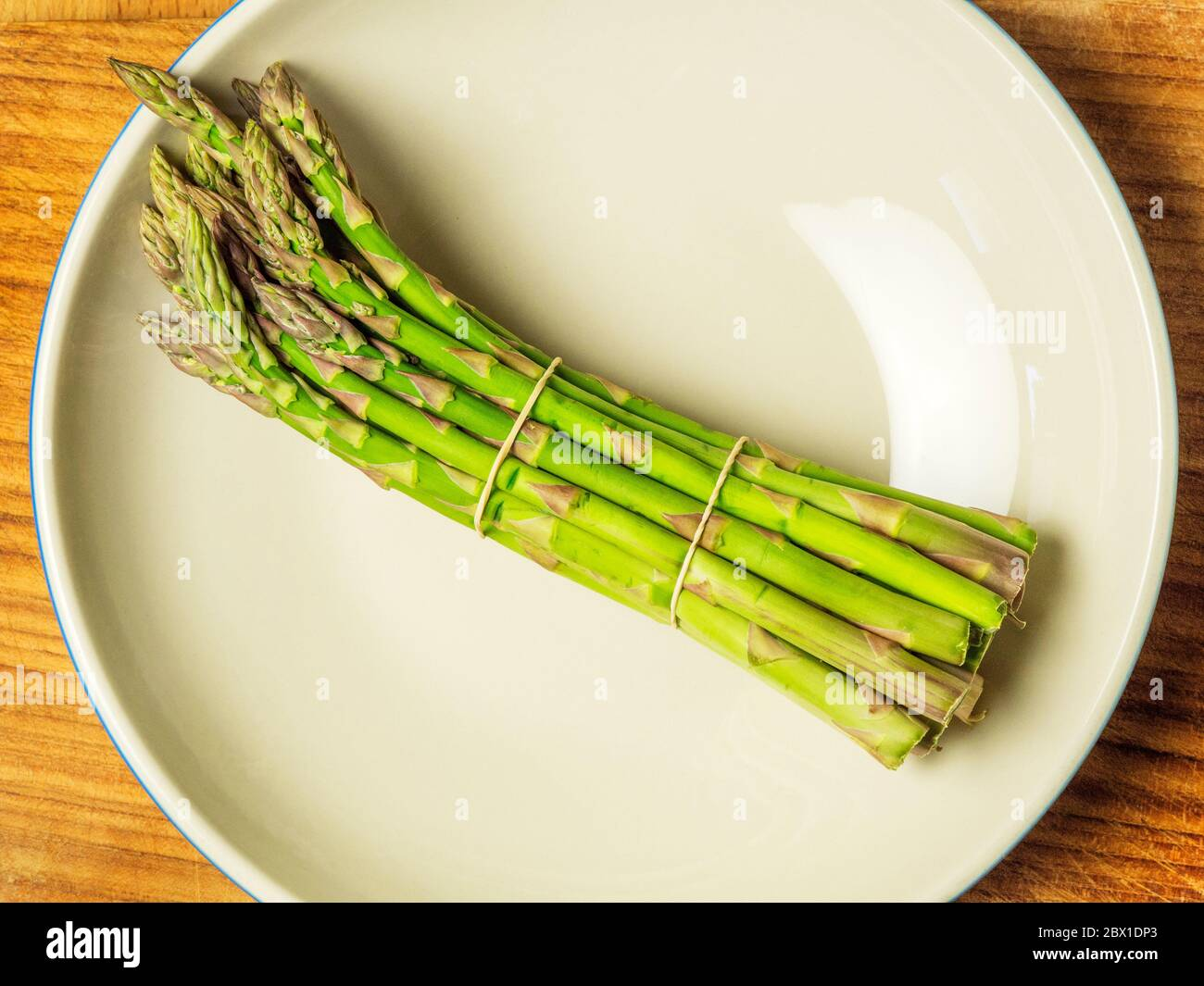 A bunch of asparagus spears in a bowl on a wooden chopping board Stock Photo
