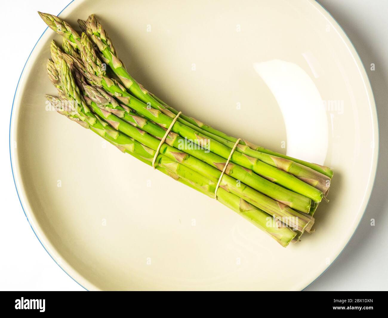 A bunch of asparagus spears in a bowl on a white background Stock Photo
