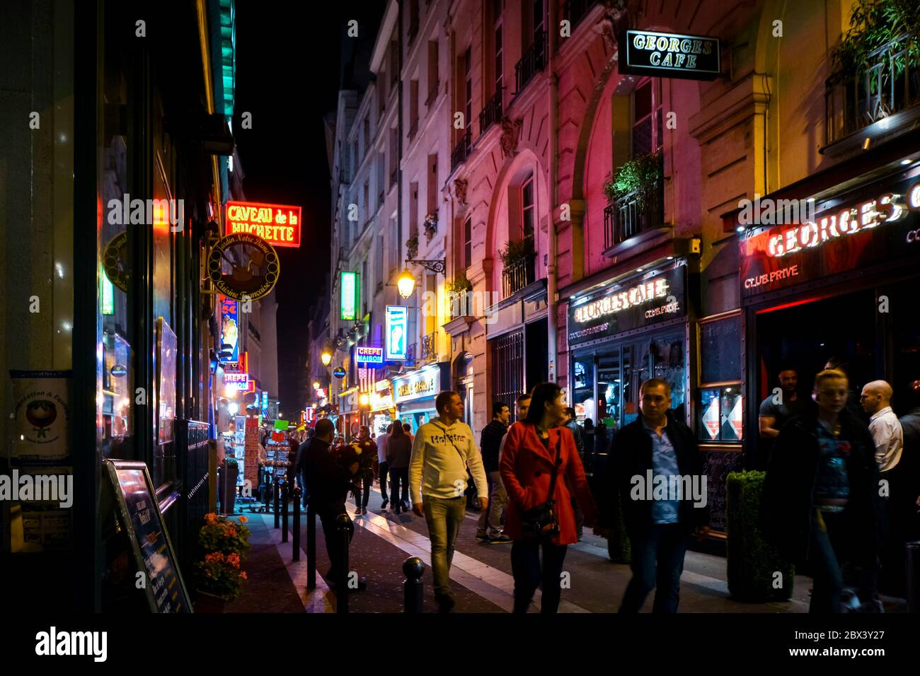 Tourists pass shops and cafes as they walk the colorful neon lit streets late at night in the Latin Quarter section of Paris France Stock Photo