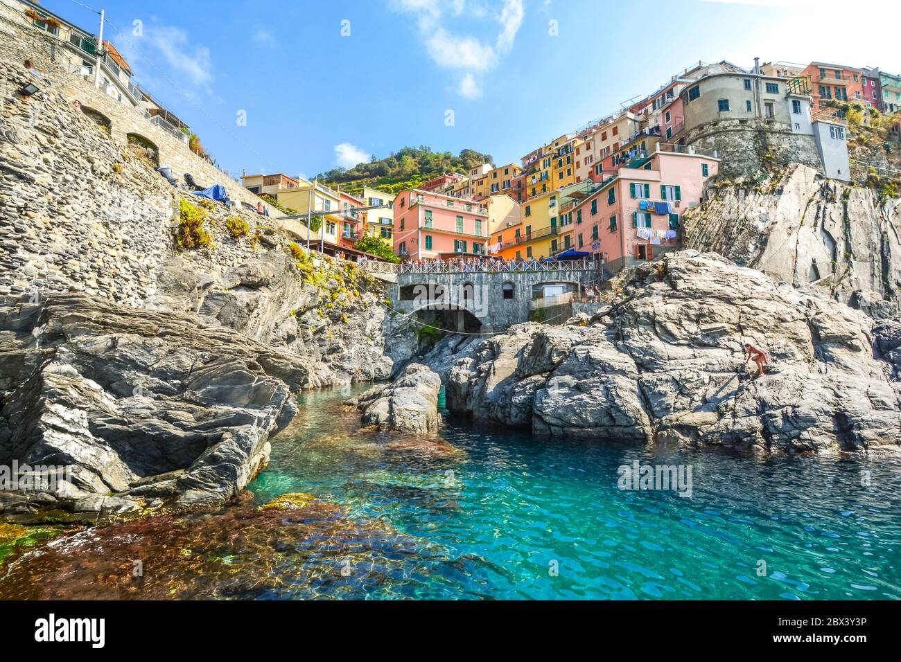 The rocky coastline and swimming bay on the Ligurian Coast of Italy at the village of Manarola, Italy, part of the Cinque Terre, an Unesco site Stock Photo