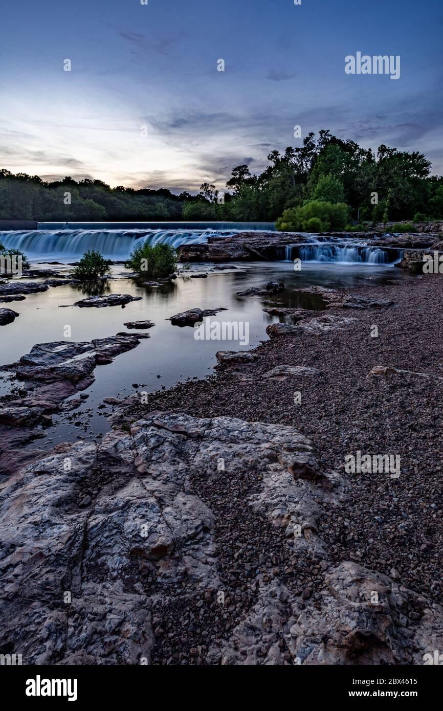 Sunset skies over Grand Falls waterfall in Joplin, Missouri Stock Photo