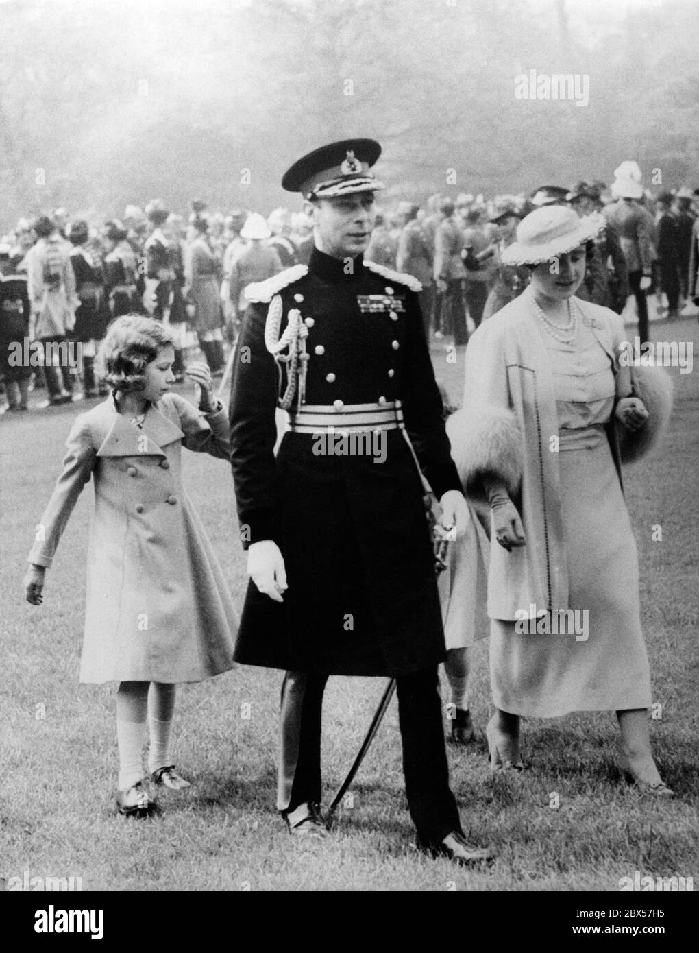 King George VI, Queen Elizabeth, Princess Elizabeth and Princess Margaret Rose ( hidden) on their way to the parade ground for the presentation of the special Coronation Medals for the Dominions and Colonial troops that will be presented at his coronation at Buckingham Palace. Over 1500 soldiers salute the Royal Family. Stock Photo