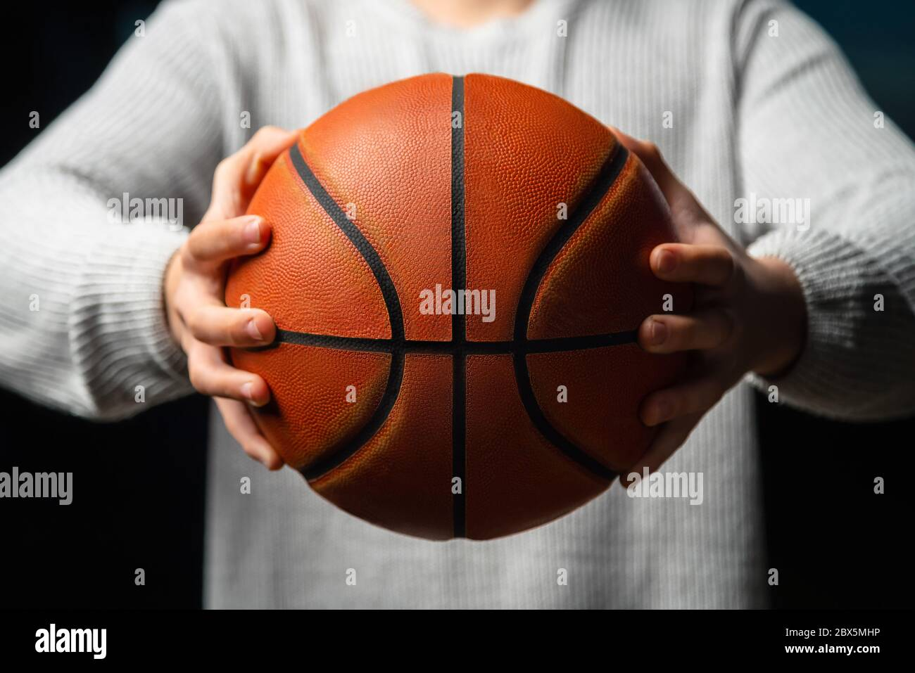 Close up of professional basketball player holding a ball in the hand. Street basketball athlete preparing for competition. Concept of success, scorin Stock Photo